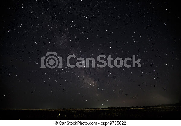 Beautiful night sky with stars. Milky Way over field - csp49735622