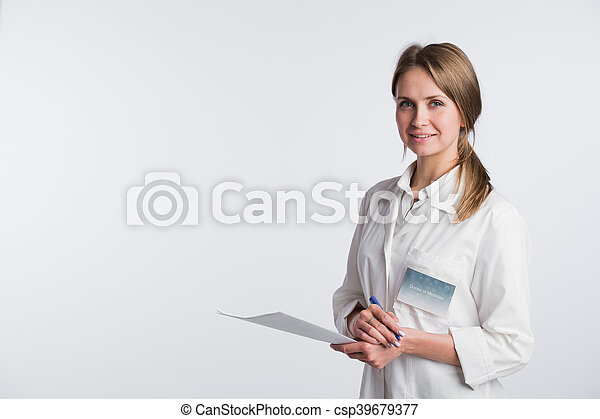 Beautiful nurse smiling and taking notes on a white isolated background - csp39679377