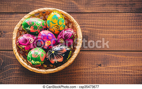 Beautiful painted colorful Easter eggs in a wickerwork basket on old brown wooden background - csp35473677
