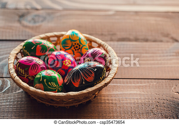 Beautiful painted colorful Easter eggs in a wickerwork basket on old brown wooden background - csp35473654