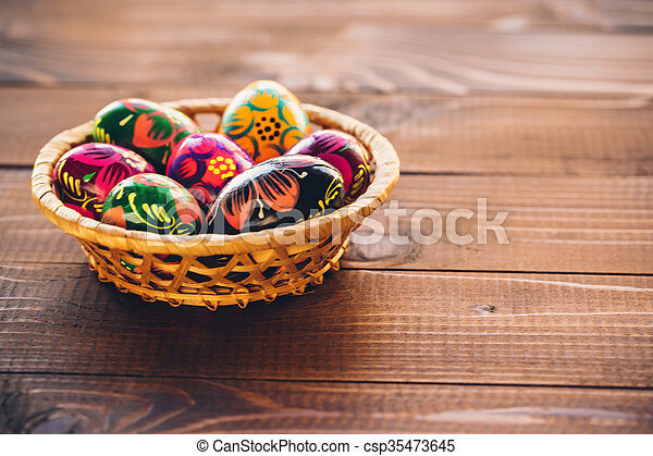 Beautiful painted colorful Easter eggs in a wickerwork basket on old brown wooden background - csp35473645