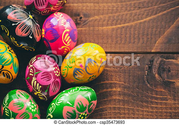 Beautiful painted colorful Easter eggs on old brown wooden background - csp35473693