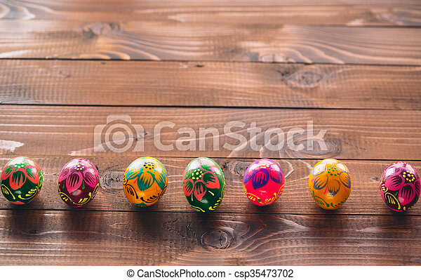 Beautiful painted colorful Easter eggs on old brown wooden background - csp35473702