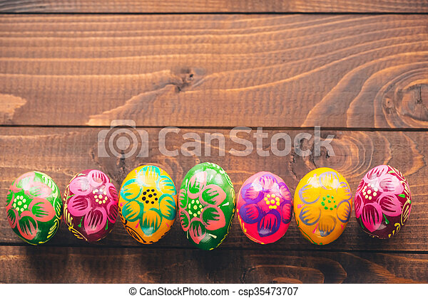 Beautiful painted colorful Easter eggs on old brown wooden background - csp35473707