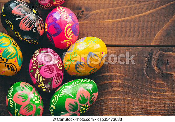 Beautiful painted colorful Easter eggs on old brown wooden background - csp35473638