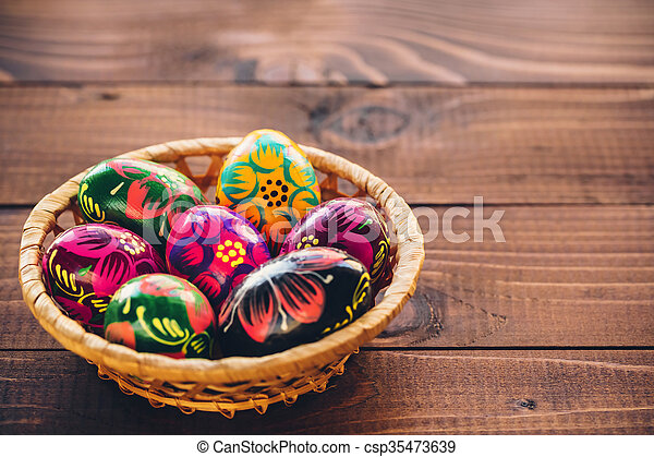 Beautiful painted colorful Easter eggs in a wickerwork basket on old brown wooden background - csp35473639