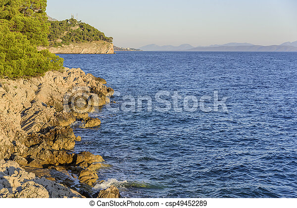 Beautiful pine trees and the shore of the blue sea in the evening. Croatia. - csp49452289