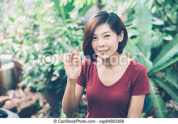 Beautiful portrait young asian woman smiling waving hand in garden at home, Friendly girl and expression positive of emotion, hello and greeting, one person, happy female excited and cheerful. - csp84663368