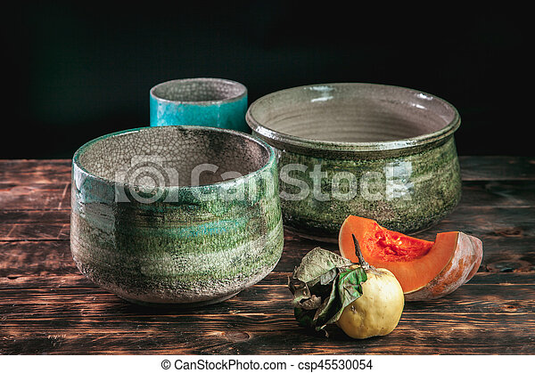 Beautiful pottery handmade on brown wooden background - csp45530054