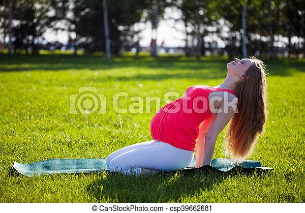 beautiful pregnant woman in yoga pose outdoor