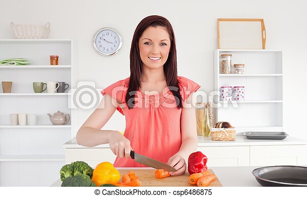 Beautiful red-haired woman cutting some vegetables in the kitchen - csp6486875