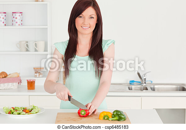 Beautiful red-haired woman cutting some vegetables in the kitchen - csp6485183