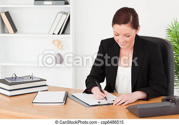 Beautiful red-haired woman in suit writing on a notepad - csp6486515