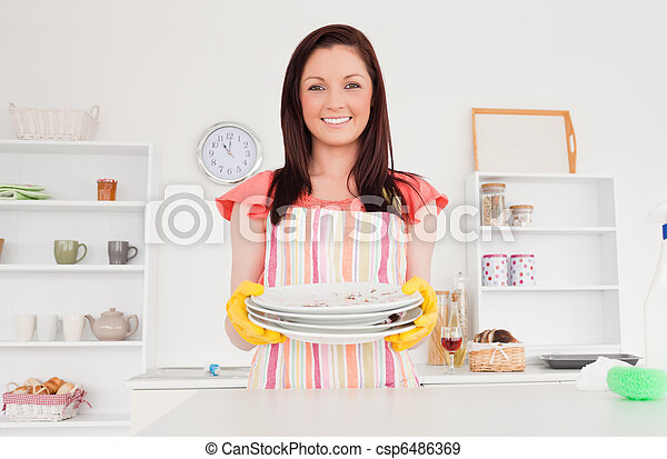 Beautiful red-haired woman posing while holding some dirty plates in the kitchen in her appartment - csp6486369