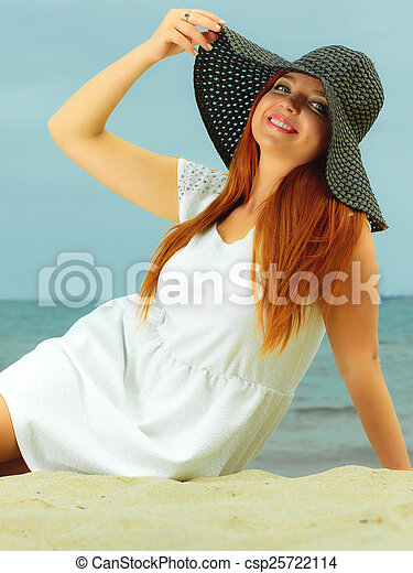 Beautiful redhaired woman in hat on beach, portrait - csp25722114