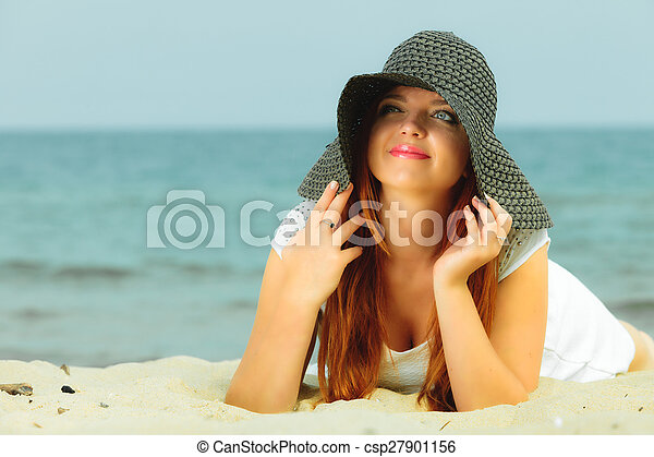 Beautiful redhaired woman in hat on beach, portrait - csp27901156