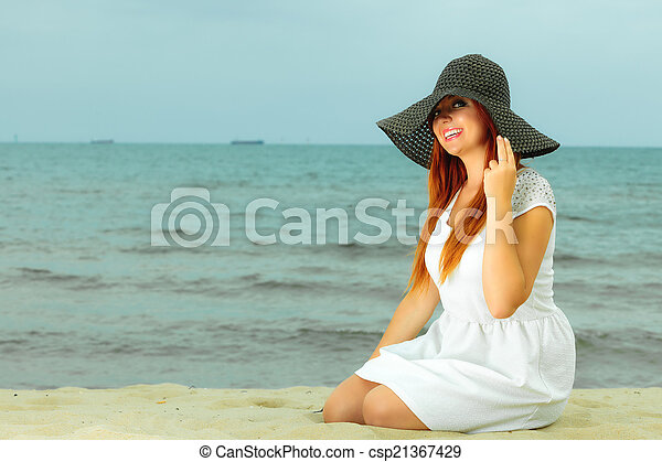 Beautiful redhaired woman in hat on beach, portrait - csp21367429