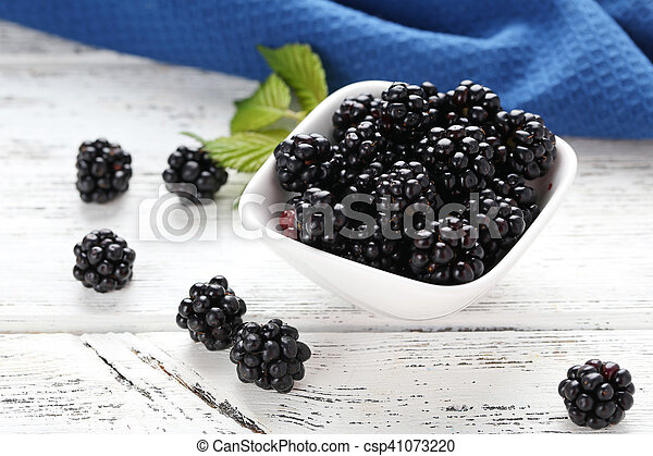 Beautiful ripe blackberry in bowl on white wooden background - csp41073220