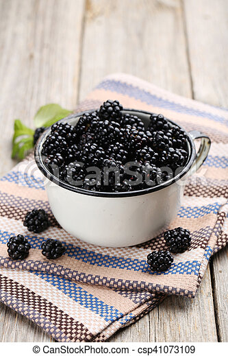 Beautiful ripe blackberry in cup on grey wooden background - csp41073109