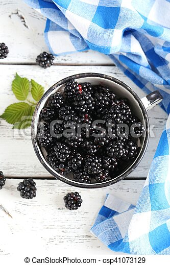 Beautiful ripe blackberry in cup on white wooden background - csp41073129