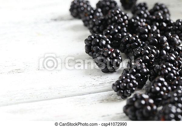 Beautiful ripe blackberry on white wooden background - csp41072990