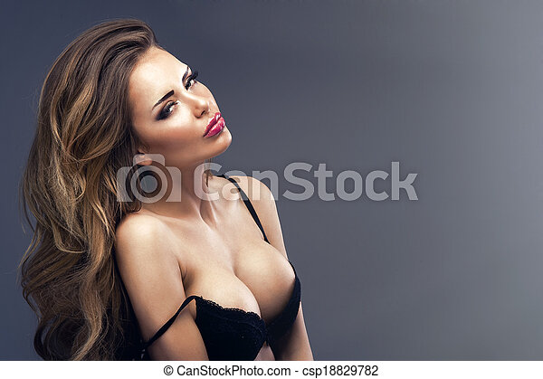 Beautiful sexy blonde woman standing, wearing black sensual lingerie, looking away. - csp18829782