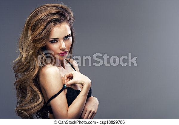 Beautiful sexy blonde woman standing, wearing black sensual lingerie, looking away. - csp18829786