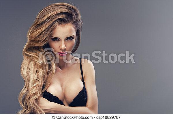 Beautiful sexy blonde woman standing, wearing black sensual lingerie, looking away. - csp18829787