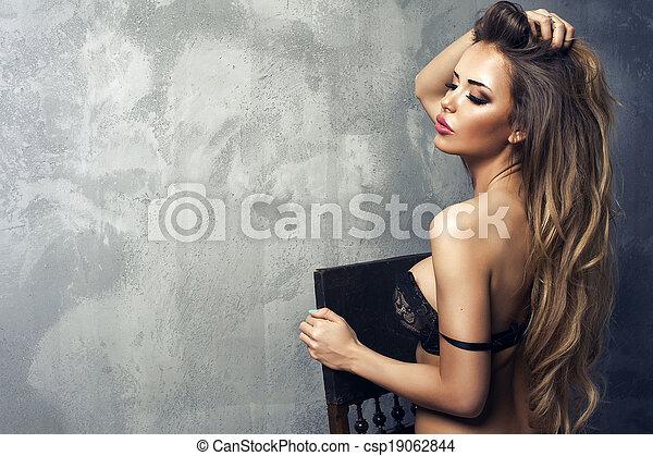Beautiful sexy blonde woman standing, wearing black sensual lingerie, looking away. - csp19062844