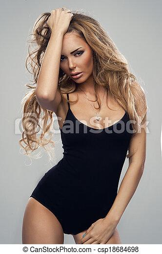 Beautiful sexy blonde woman standing, wearing black sensual lingerie, looking away. - csp18684698