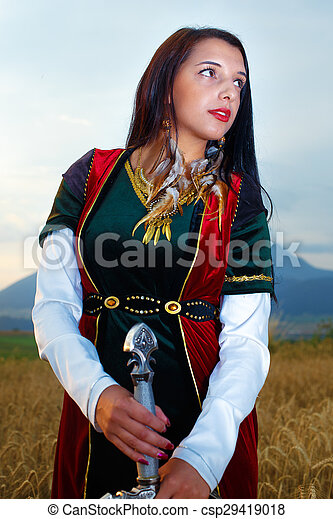 Beautiful  sexy woman warrior with sword.  land background. - csp29419018