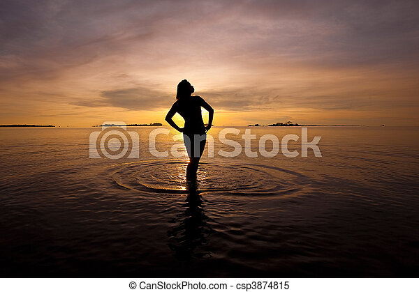 Beautiful silhouette of woman  in shallow water during sunrise - csp3874815