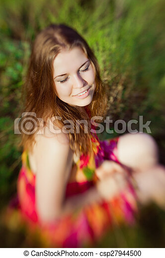 Beautiful smiling ginger girl with closed eyes sitting on grass in summer park on sunny day. Selective focus on one eye, lensbaby blur effect. Relax and rest concept - csp27944500