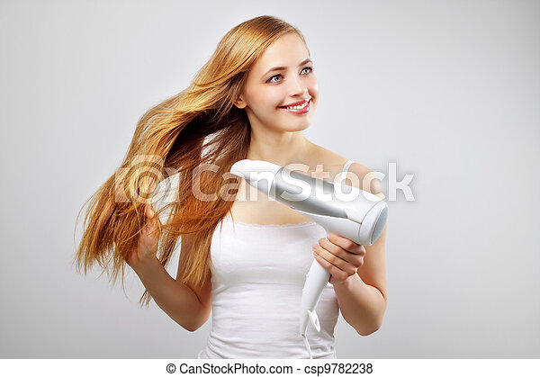 Beautiful smiling girl drying her hair with a blow dryer - csp9782238