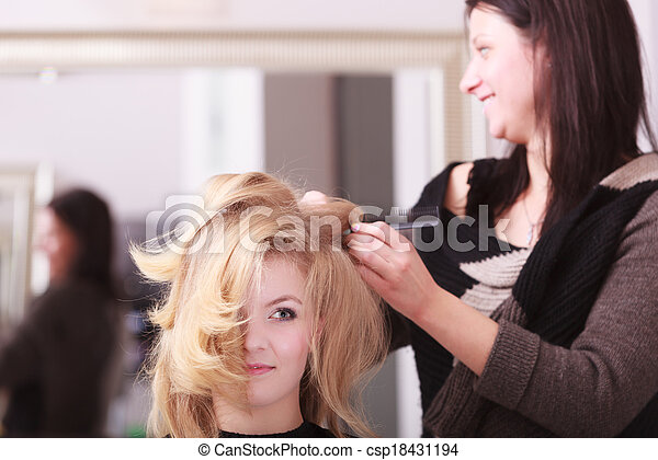 Beautiful smiling girl with blond wavy hair by hairdresser. Hairstylist with comb combing female client young woman in hairdressing beauty salon. Hairstyle. - csp18431194