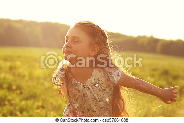 Beautiful smiling kid girl trying to fly with happy look on nature bright sunset summer background. Closeup portrait - csp57661088