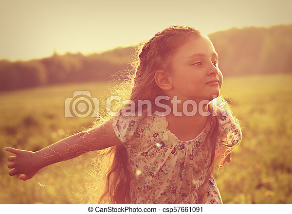 Beautiful smiling kid girl trying to fly with happy look on nature bright sunset summer background. Closeup toned portrait - csp57661091