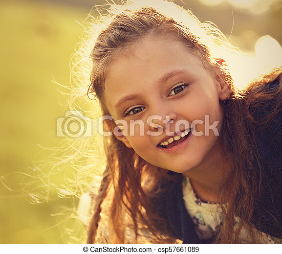 Beautiful smiling kid girl with happy look on nature summer green tree background. Closeup toned bright portrait - csp57661089