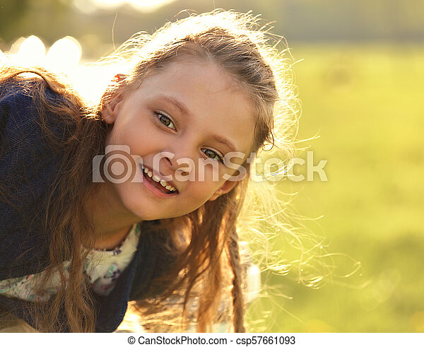 Beautiful smiling kid girl with happy look on nature bright summer green tree background. Closeup portrait - csp57661093