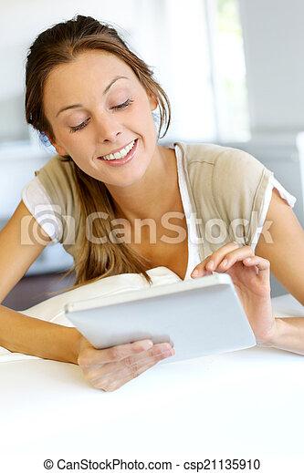 Beautiful smiling woman using digital tablet at home - csp21135910