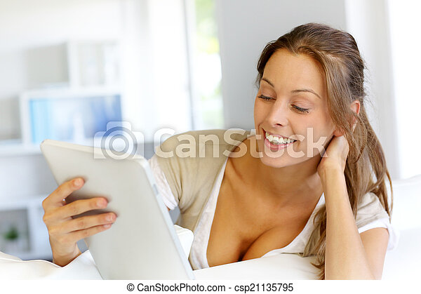 Beautiful smiling woman using digital tablet at home - csp21135795