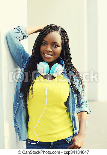 Beautiful smiling young african woman with headphones in city - csp34184647