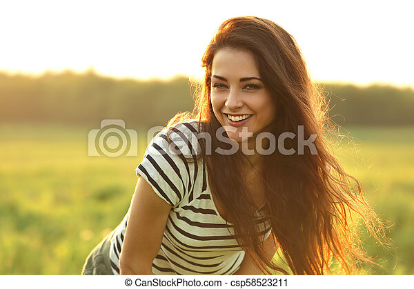 Beautiful smiling young woman looking happy with long amazing hair on nature bright sunset summer background. Closeup portrait - csp58523211