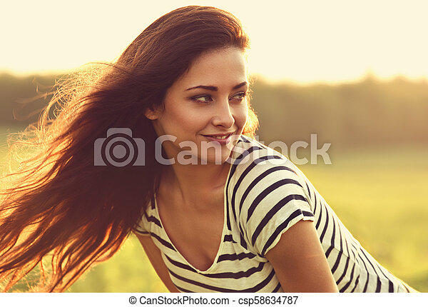 Beautiful smiling young woman looking happy with long amazing bright hair on nature bright sunset summer background. Closeup toned color portrait - csp58634787