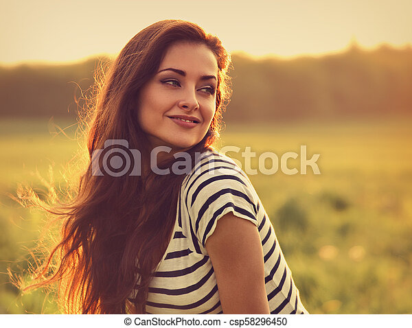 Beautiful smiling young woman looking happy with long amazing hair on nature bright sunset summer background. Closeup toned color portrait - csp58296450