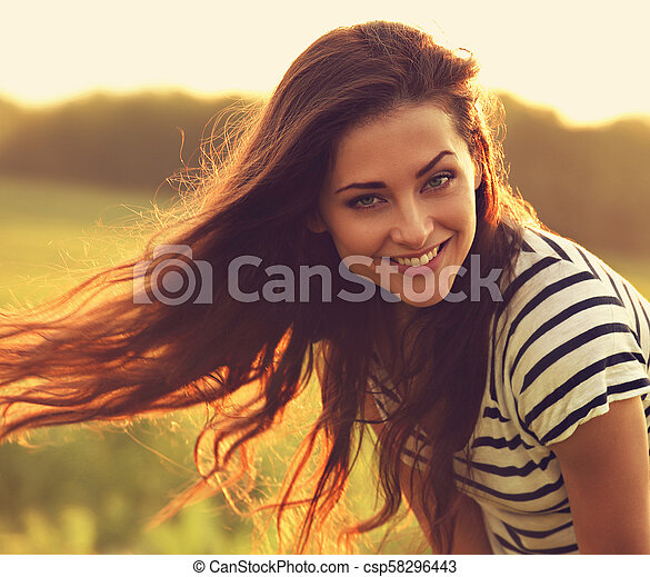 Beautiful smiling young woman looking happy with long amazing hair on nature bright sunset summer background. Closeup bright toned portrait - csp58296443