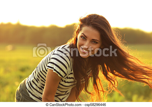 Beautiful smiling young woman looking happy with long amazing hair on nature bright sunset summer background. Closeup bright portrait - csp58296446