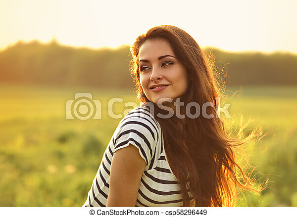 Beautiful smiling young woman looking happy with long amazing hair on nature bright sunset summer background. Closeup portrait - csp58296449