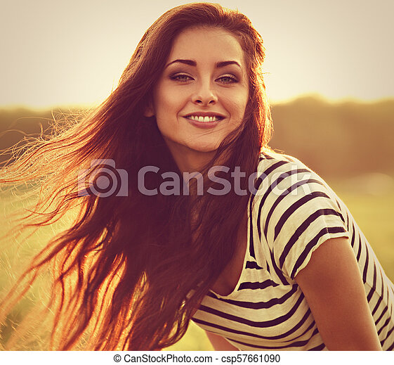 Beautiful smiling young woman looking happy with long amazing hair on nature bright sunset summer background. Closeup toned portrait - csp57661090