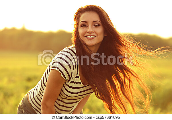 Beautiful smiling young woman looking happy with long amazing hair on nature bright sunset summer background. Closeup portrait - csp57661095